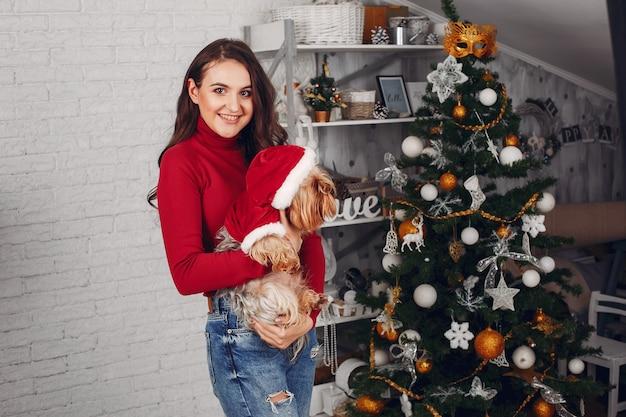 Elegante dame die zich dichtbij kerstboom bevindt Gratis Foto