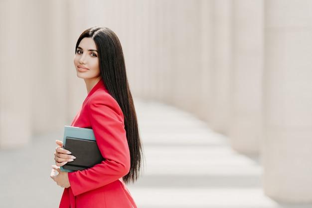 Elegante donkerbruine dame met donker lang steil haar, gekleed in modieus rood pak Premium Foto