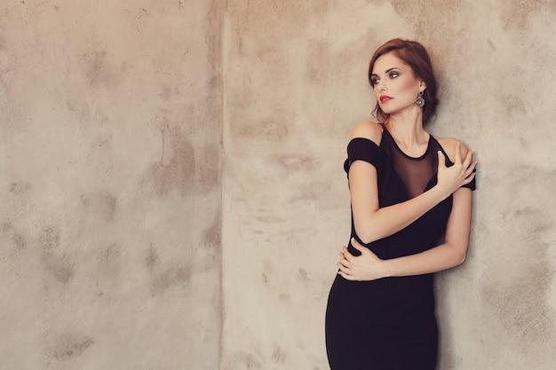 Elegante en glamoureuze vrouw met zwarte jurk poseren, mode concept Gratis Foto