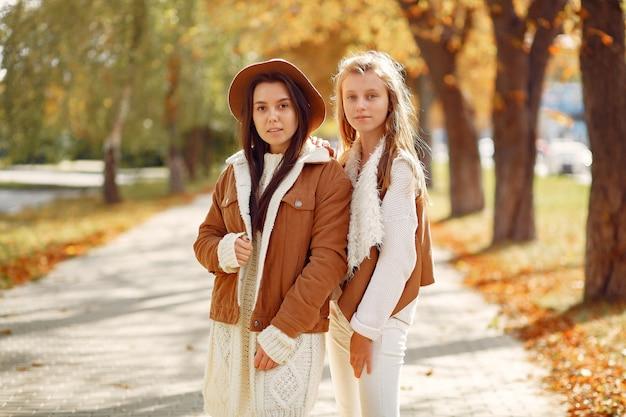 Elegante en stijlvolle meisjes in een herfst park Gratis Foto