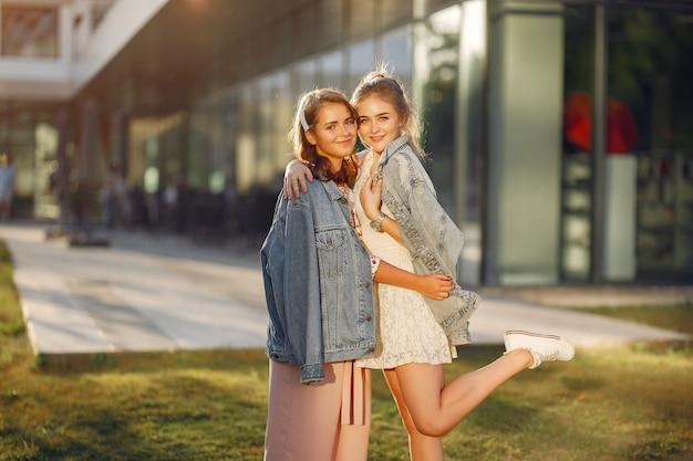 Elegante en stijlvolle meisjes in een zomerpark Gratis Foto