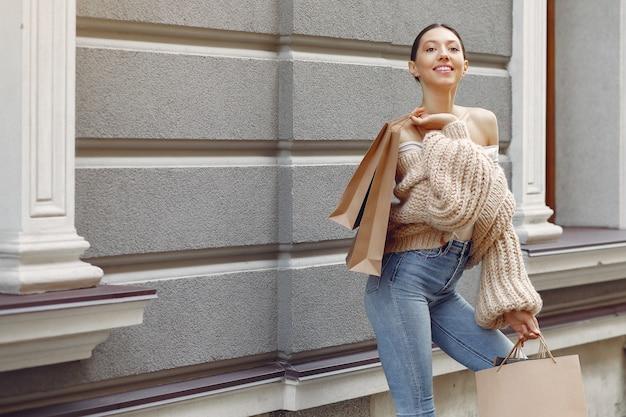 Elegante en stijlvolle meisjes op straat met boodschappentassen Gratis Foto