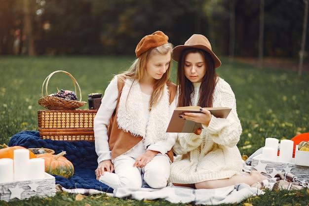 Elegante en stijlvolle meisjes zitten in een herfst park Gratis Foto