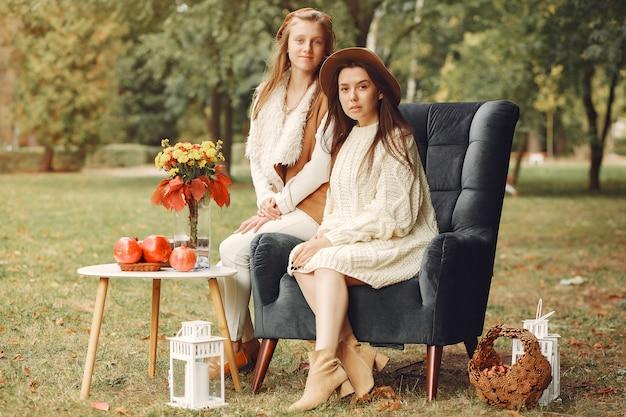 Elegante en stijlvolle meisjes zitten op een stoel in een park Gratis Foto