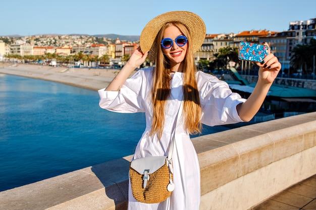 Elegante glamour prachtige vrouw, gekleed in luxe witte jurk en stro accessoires selfie maken op het strand Gratis Foto