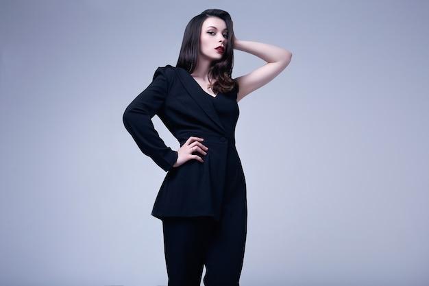 Elegante gotische donkerbruine vrouw met rode lippen in zwart kostuum Premium Foto
