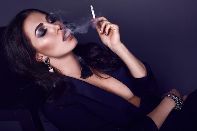 Elegante hete donkerbruine vrouw die een sigaret rookt Premium Foto