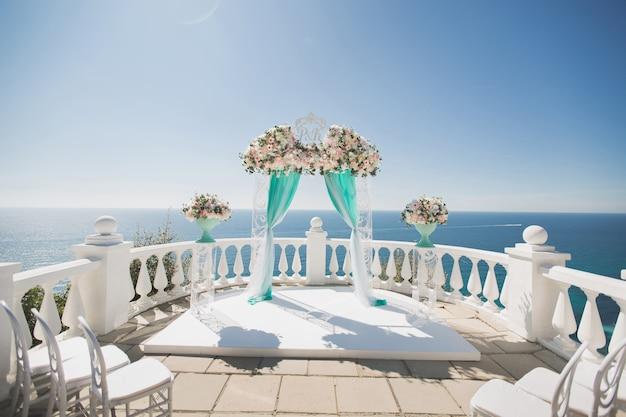 Elegante huwelijksboog met verse bloemen, vazen op de oceaan en de blauwe hemel. Premium Foto
