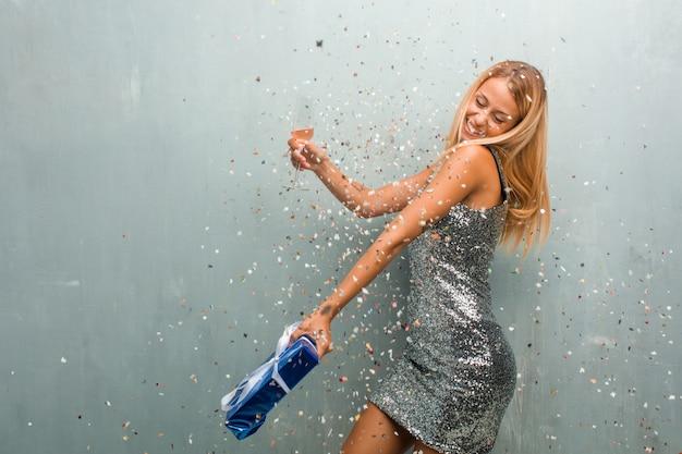 Elegante jonge blonde vrouw viert nieuw jaar met champagne, een geschenk en confetti. Premium Foto