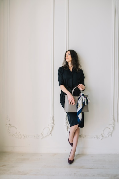 Elegante jonge vrouw in jurk met handtas in de buurt van de muur in de kamer Gratis Foto