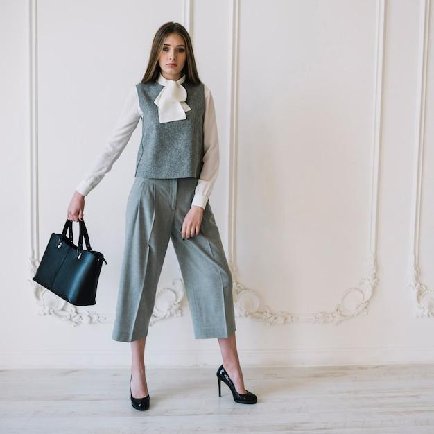 Elegante jonge vrouw in kostuum met handtas in de kamer Gratis Foto