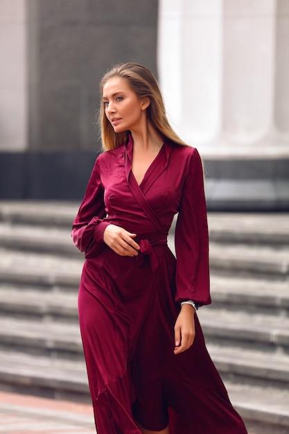Elegante jongedame in lange bordeauxrode jurk met mouwen en tailleband. hand vasthouden onder de borsten. blond kapsel en natuurlijke naaktmake-up. lopend door de straat bij het gebouw. Gratis Foto