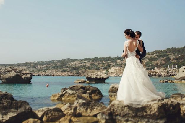 Elegante lachende jonge bruid en bruidegom poseren op de rotsen op het strand Gratis Foto