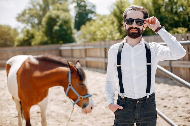 Elegante man die naast paard in een boerderij Gratis Foto