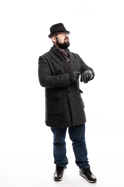 Elegante man met een baard in een jas en hoed kijkt op zijn horloge. volledige hoogte. witte muur. verticaal. Premium Foto