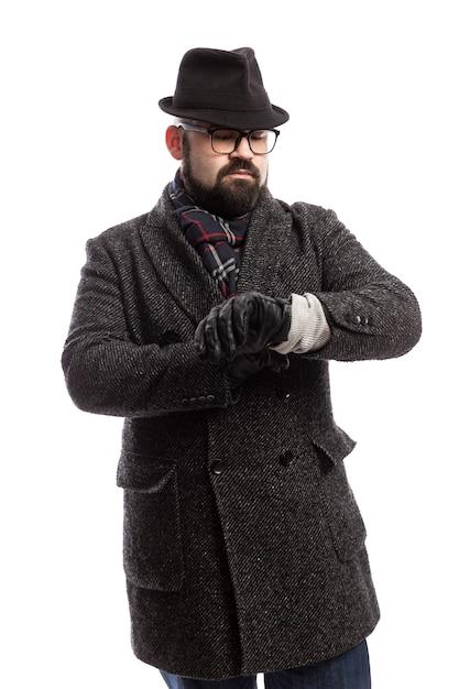 Elegante man met een baard in een jas en hoed kijkt op zijn horloge. witte muur. verticaal. Premium Foto