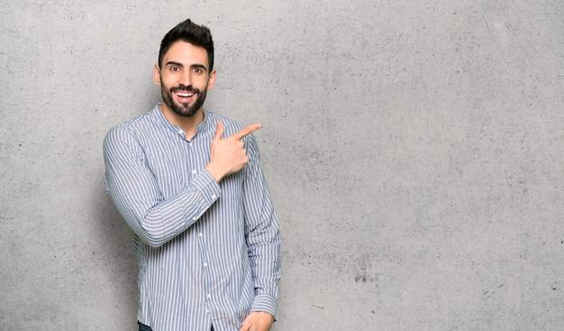 Elegante man met shirt naar de zijkant gericht om een product textuur muur te presenteren Premium Foto