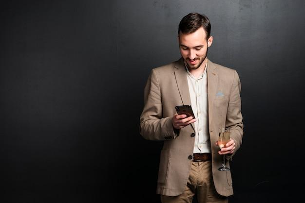 Elegante man op feestje kijken naar telefoon Gratis Foto