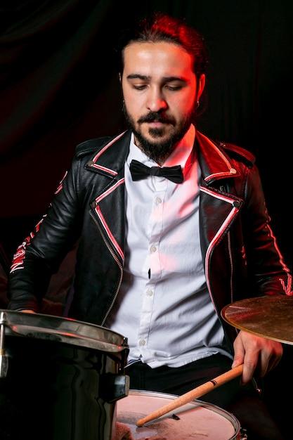 Elegante man spelen op drumstel Gratis Foto