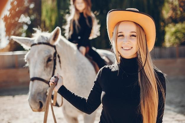 Elegante meisjes met een paard in een boerderij Gratis Foto