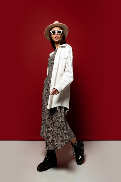 Elegante modieuze vrouw in witte jas en jurk poseren. enkellaars in zwart leer. volledige lengte. Gratis Foto