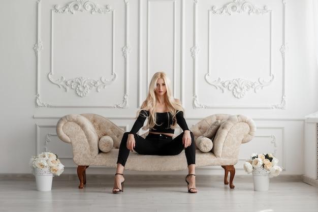 Elegante mooie jonge stijlvolle vrouw in zwarte modieuze kleding met schoenen, zittend op een bank met bloemen in een witte vintage studio Premium Foto