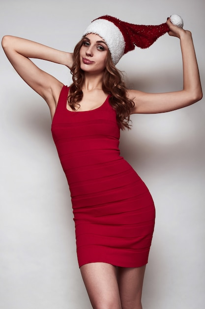 Elegante mooie vrouw in een rode jurk en kerstmuts Premium Foto