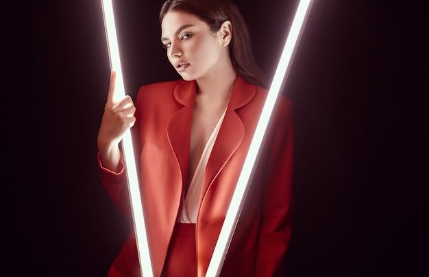 Elegante mooie vrouw in een rode modieuze pak poseren met neonlichten Premium Foto