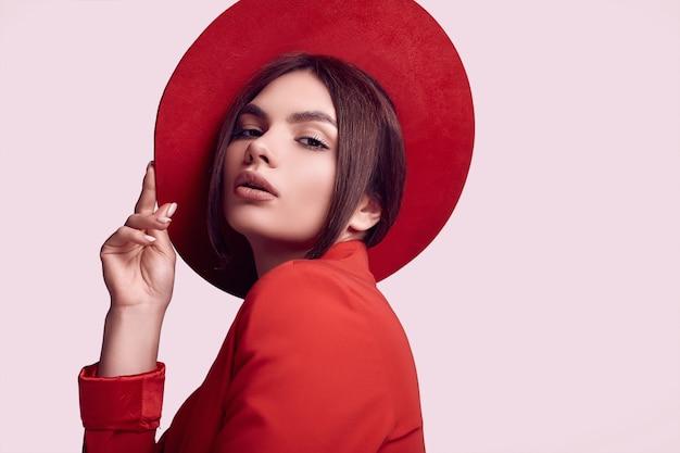 Elegante mooie vrouw in een rood modieus pak en brede hoed Premium Foto
