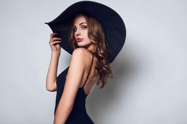 Elegante mooie vrouw in een zwarte jurk en hoed Premium Foto