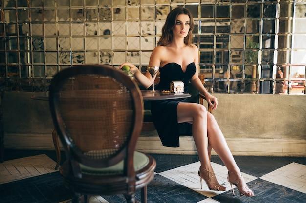 Elegante mooie vrouw zitten in vintage café in zwart fluwelen jurk, avondjurk, rijke stijlvolle dame, elegante modetrend, sexy verleidelijke look, aantrekkelijk mager figuur met lange benen in hakken Gratis Foto