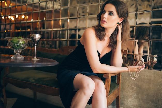 Elegante mooie vrouw zitten in vintage café in zwart fluwelen jurk, avondjurk, rijke stijlvolle dame, elegante modetrend, wachten op een datum, kleine gouden handtas in de hand houden Gratis Foto