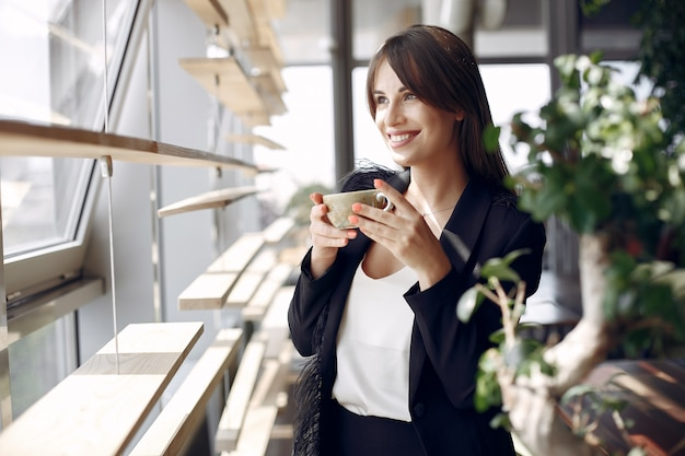 Elegante onderneemster die in een bureau werkt en een koffie drinkt Gratis Foto