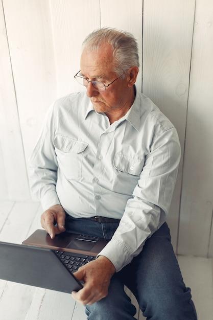 Elegante oude man om thuis te zitten en een laptop te gebruiken Gratis Foto