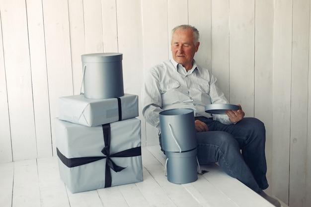 Elegante oude man om thuis te zitten met kerstcadeautjes Gratis Foto