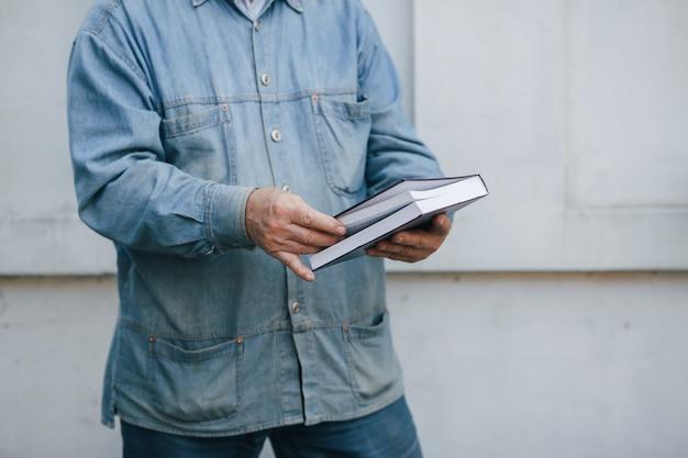 Elegante oude man permanent op grijze achtergrond met een boek Gratis Foto