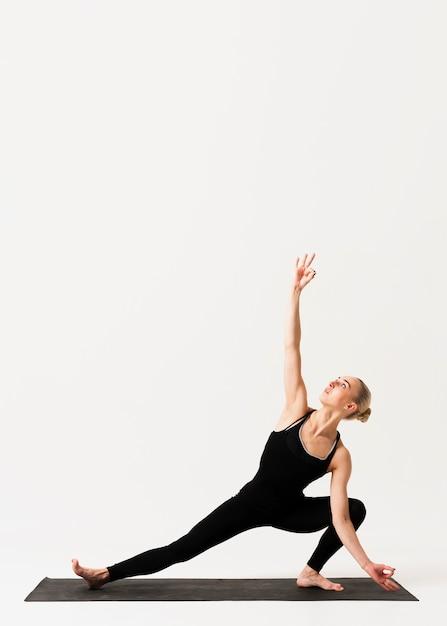 Elegante positie bij yogales indoor Gratis Foto
