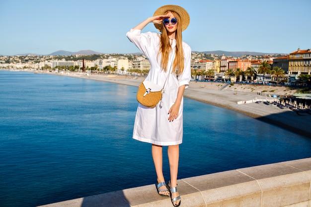 Elegante sensuele zalige blonde vrouw poseren voor een prachtig uitzicht op het mooie strand van de franse rivièra Gratis Foto