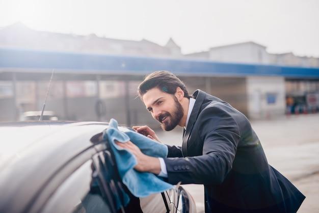 Elegante stijlvolle jonge bebaarde man in pak achterruit van de auto met een blauwe microfiber doek schoonmaken. Premium Foto