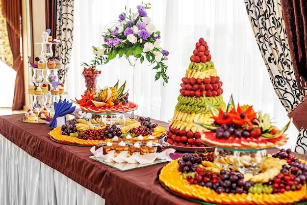 Elegante tafel met fruit en gebak. het concept van een feest, eten Premium Foto