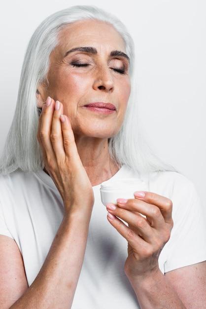Elegante volwassen vrouw die vochtinbrengende crème toepast Gratis Foto