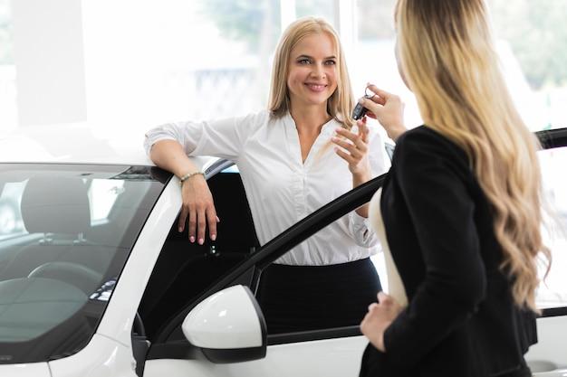 Elegante vrouw die de autosleutels in autotoonzaal ontvangt Gratis Foto
