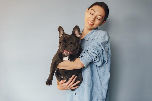 Elegante vrouw in een blauw shirt met zwarte bulldog Gratis Foto