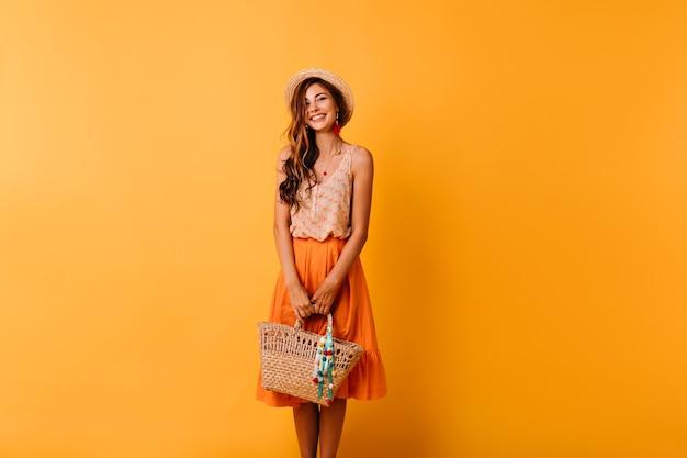 Elegante vrouw in zomer outfit vakantie voorbereiden. romantisch gembermeisje in strohoed die op sinaasappel met zak stellen. Gratis Foto