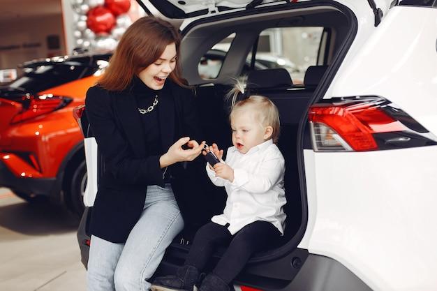 Elegante vrouw met dochtertje in een auto salon Gratis Foto