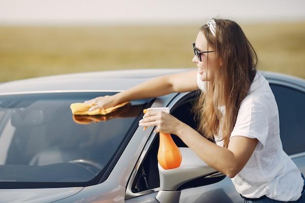 Elegante vrouw veegt de auto af met een doek Gratis Foto