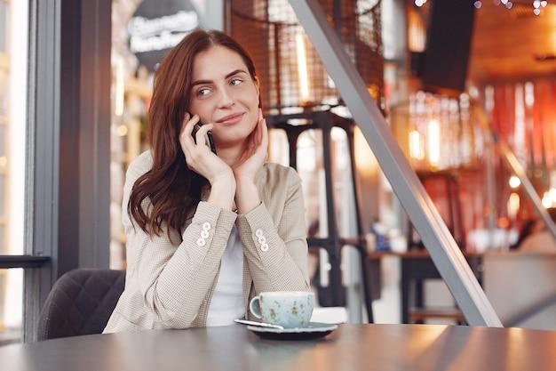 Elegante vrouw zitten aan de tafel met een telefoon Gratis Foto