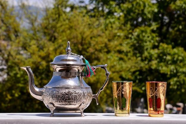 Elegante zilveren theepot met gouden glaasjes Gratis Foto