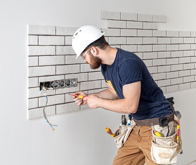 Elektricien bouwvakker met een baard in overall tijdens de installatie van stopcontacten. home renovatie concept. Gratis Foto