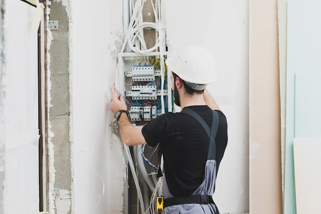 Elektricien die met draden in schakelbord werkt Gratis Foto